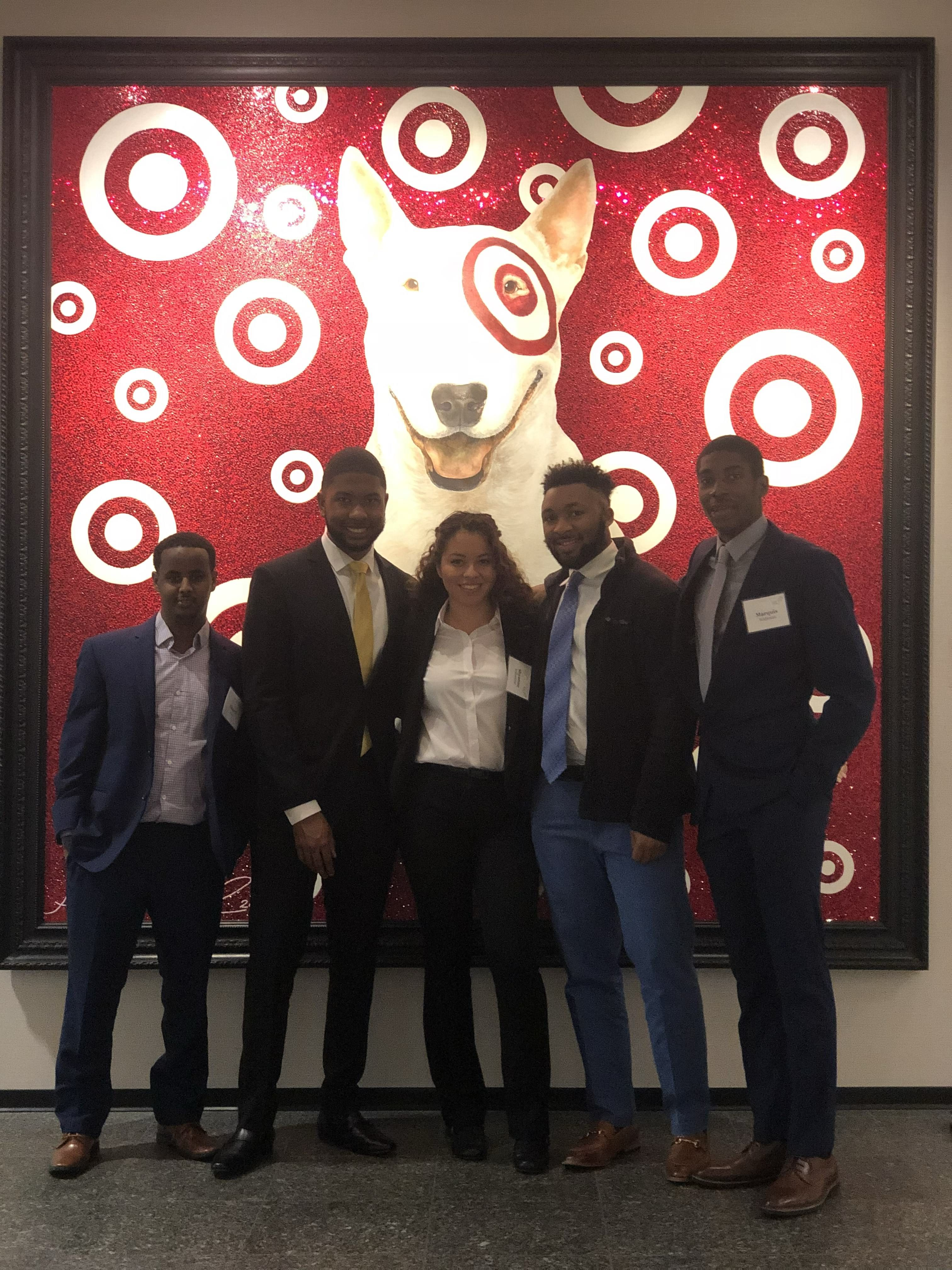 Shyanne Yellowbird poses with Career Prep peers and a portrait of Bullseye, the Target mascot, at MLT's Interview and Analytical Skills seminar at Target.