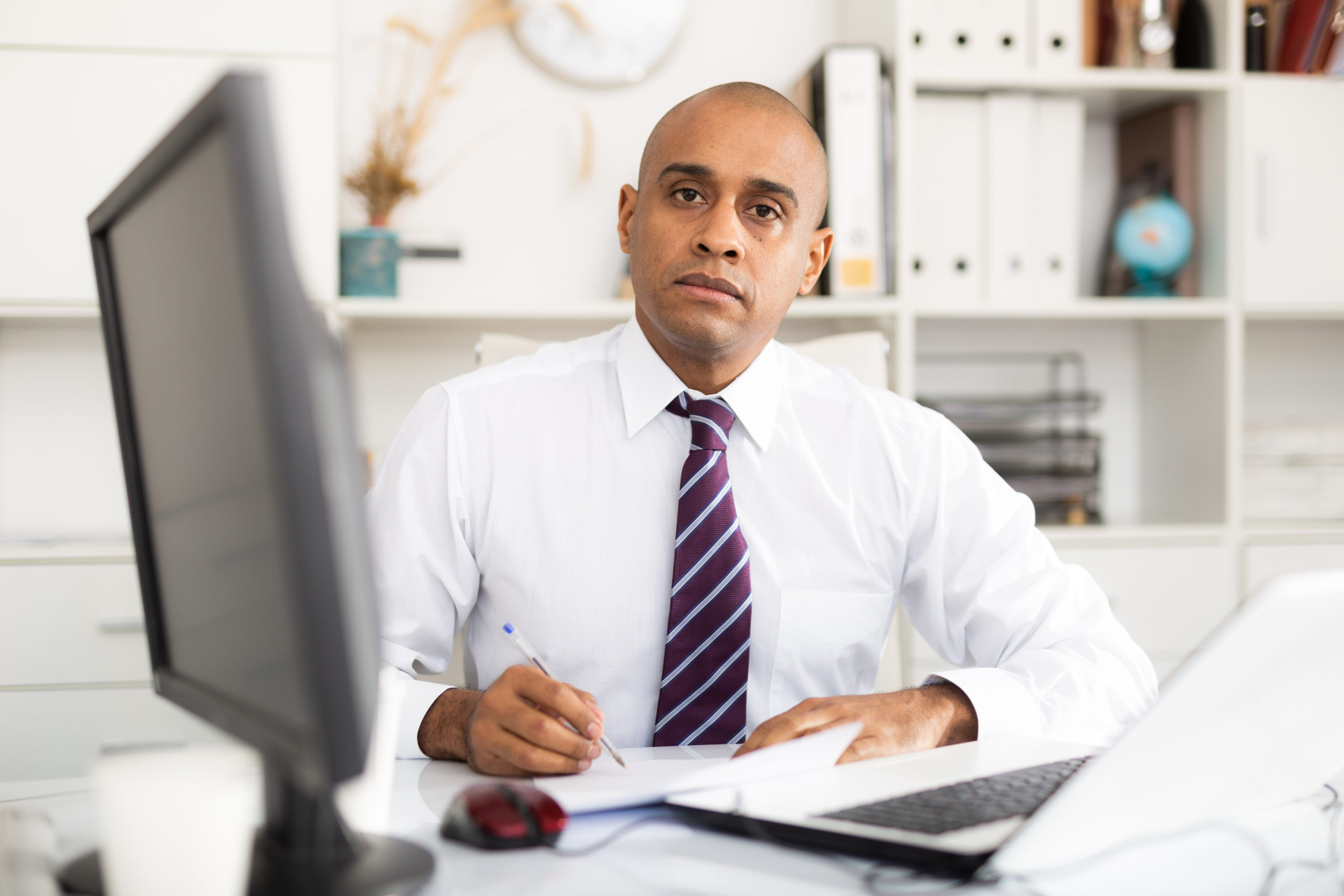Professional business man using laptop at workplace in office